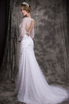 Luxurious and intricate. This fit-and-flare silhouette gown features illusion sweet-heart neckline and a long illusion sleeves. It is also highlighted with delicate hand-sewn silver flowers from bodice to knees, with beaded Embellishments on top. It has a sexy open back with beaded waist band. Sweep train.  #junepeonybridal #birmingham #wedding #dresses #bride #fitandflare #sleeves #weddingideas #fashion #style #boutique
