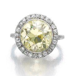 DIAMOND RING, CIRCA 1900. Set with a circular-cut diamond of yellow tint within a border of near colourless single-cut diamonds, size 46, sizing beads.