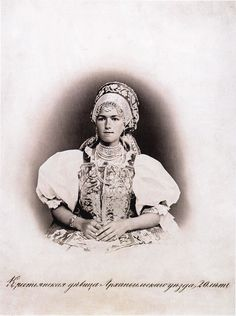 20-years-old peasant maiden from Archangelsk region in traditional Russian costume of Archangelsk area. shirt, epanechka/ dushegreya (bodice), necklace (pearls) and headdress. vintage/ old photo of Russia