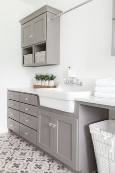 Gray shaker laundry room cabinets with glass knobs surrounding a white apron sink topped with white quartz countertops. Gray shaker laundry room cabinets with glass knobs surrounding a white apron sink topped with white quartz countertops. Kitchen Cabinet Doors, Laundry Mud Room, White Apron Sink, Interior, Grey Laundry Rooms, Farmhouse Furniture, Farmhouse Kitchen Cabinets, Kitchen Styling, Farmhouse Style House