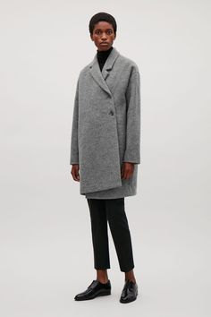 A relaxed, wrap-over style, this coat is made from warm wool with a smooth lining. Designed in a cocoon shape, it has dropped shoulders, a wrap-over front and double-breast fastenings.