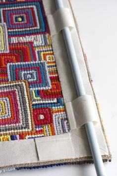 Using canvas to bind and hand a hooked rug. Interesting