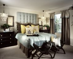 Opulent master bedroom decorating ideas with black furniture and big black pillows. Two chairs in front of the bed with a multicolored pillow. The night lights are bolted to the ceiling for a great design idea.