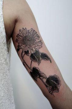 Tatouage en noir d'une tournesol https://tattoo.egrafla.fr/2016/02/02/modeles-tatouage-tournesol/
