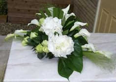 Funeral arrangement - big green leaves: we are carried