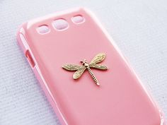 A hand-hammered 22kt gold plated dragonfly pendant laid on our pink hard shell case. Handmade to order!