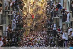 SPAIN, Pamplona: People standing on balconies look at participants as they run in front of Alcurrucens bulls during the first bull run of the San Fermin Festival, on July 7, 2013, in Pamplona, northern Spain. The festival is a symbol of Spanish culture that attracts thousands of tourists to watch the bull runs despite heavy condemnation from animal rights groups. AFP PHOTO / PEDRO ARMESTRE