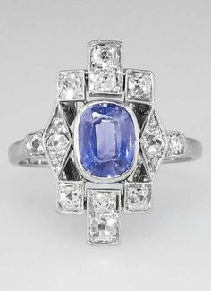 Transcendent 1920s Ceylon Sapphire & Diamond Ring 10k, comprised of a center bezel-set, oval cut sapphire, surrounded by twelve Old European cut, old mine cut, and single cut diamonds, bead-set within geometric-shaped frames with milgrain edging.