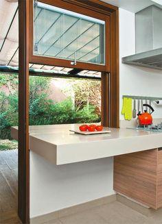 A bancada de Corian (DuPont) faz a conexão entre a cozinha principal e a varanda, área sombreada por um pergolado com vidros duplos e cortina retrátil (Arthur Decor).