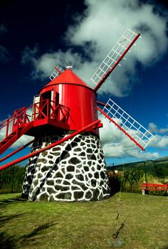 """Windmill in Faial, Azores  How many of these did I see growing up?  I think we even had a toy-like replica at one point.  I love wind, especially listening to it move through the trees, like whispers to my soul.  This windmill with its """"wholey"""" blades reminds me of our vulnerabilities.  We aren't solid form, energy passes through us but the whispers on the wind can still move us to extraordinary heights.  It reminds me to live on purpose!"""