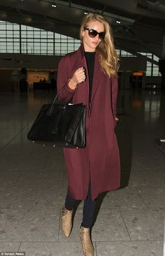 Groomed: Rosie Huntington-Whiteley makes her way through Heathrow on Thursday looking as polished as ever