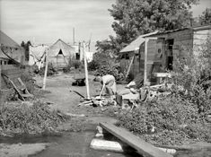 "July 1936. ""Migratory fruit pickers' camp in Yakima, Washington."" Dust Bowl refugee from the Midwest hammering away at packing crate scraps outside her tent."