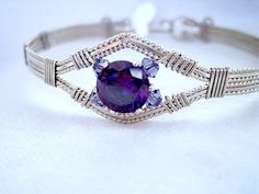 In this bracelet is a purple CZ (cubic Zirconia) gemstone, I added some Swarovski bicon beads. I wire wrapped it in Sterling Silver Filled wire.