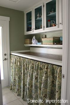 DIY laundry room on a budget - raised chicken wire cabinets, counter made from leftover wood flooring and trim, curtains to hide washer and dryer.