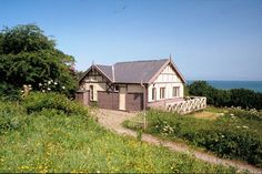 Book your stay at Castle Bungalow, a Boulton and Paul prefab with snug wood-lined rooms and stunning views of the ocean. North Devon, Stunning View, Prefab, Weekend Getaways, Bungalow, Places To Go, Castle, Real Estate, Cottage