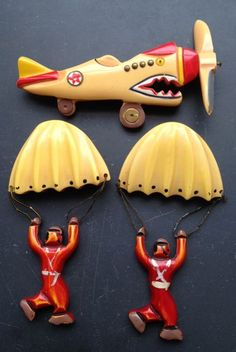 Bakelite pins - a comical airplane with moveable propeller and two paratroopers