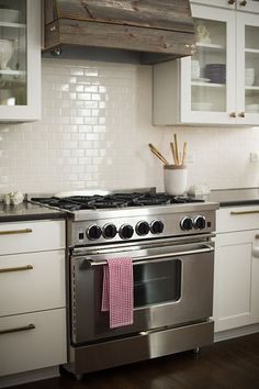 Love the glass doors, the subway tile and the rustic vent hood over a gas oven.