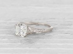 Vintage Art Deco engagement ring made in platinum and ceneterd with a GIA certified F color SI1 clarity old asscher cut diamond. Accented by two triangle cut diamonds and 4 single cuts. Circa 1930 This asscher cut stone is just sexy! Set in a simple yet detailed band the center diamond steals the show, as it should. Classic Art Deco. Learn more about Art Deco rings Diamond and gold mining has caused devastation in areas such as Africa, wreaking havoc on delicate ecosystems and communities…