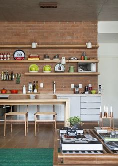 Open plan kitchen and dining space with exposed brick wall and eclectic vibe