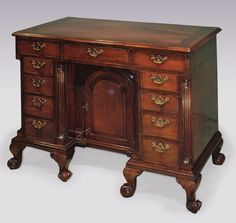 A mid 18th Century figured mahogany Kneehole Chest, having mitred, crossbanded and moulded edged top, above various graduated drawers, flanked by fluted column corners, with central arched, fielded, panelled door, supported on unusual short scrolled cabriole legs. Circa: 1750 Ref: PQ Kneehole