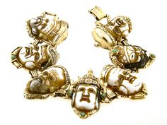 Japanese Bracelet with 7 Immortal or Gods of Fortune Faces  This 1950s bracelet is spectacular, featuring the seven Gods of Fortune. The milk glass faces and gold plated setting are in excellent vintage condition. The bracelet measures 7 1/2″ long and nearly 1/2″ wide.