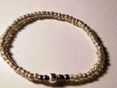 Silver and gray seed beaded elastic bracelet with a larger silver tone bead in the center.