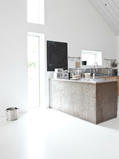 Clean white walls and flooring, juxtaposed with a raw and unpolished wooden kitchen counter. Also focus on the combination of metal, wood, and chalkboard.