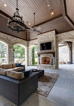 Gorgeous covered patio with natural stone fireplace and arched ...