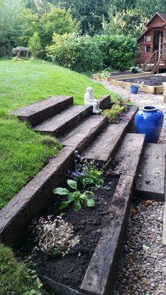 Old railway sleepers for steps and terraced flower beds transformed a boring grassy slope which was