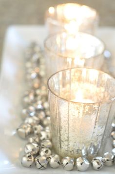 Cute decorating idea for Christmas. Simply put some votive cups in a glass tray and add inexpensive jingle bells.
