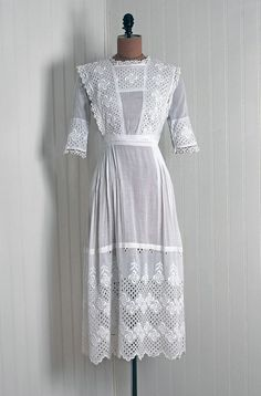 Tea Gown: 1910's, semi-sheer embroidered cotton eyelet and lace trim, pinafore bib sculpted bodice, pleat-detailed scalloped hemline skirt.