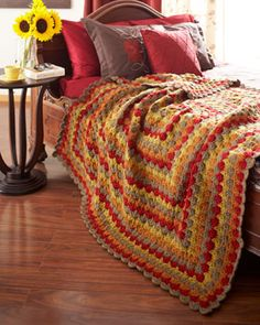 A Catherine Wheel pattern makes this cozy blanket a home decor standout. Shown in Waverly for Bernat.