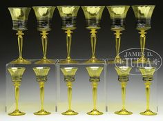 "Lot consists of six Steuben bristol yellow goblets and six Steuben bristol yellow wine glasses. Each piece has a hollow blown stem, inverted saucer foot and flaring bowl. The pieces are further decorated with applied black threading surrounding the bottom half of the bowl. Three of the wine glasses are signed and five of the goblets are signed ""Steuben"". SIZE: Goblets are 9-1/4"" t. Wines are 7-1/2"" t.- by James D. Julia"