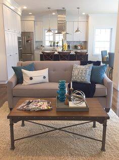 Love this combo! Gray sofa with ivory shag rug and industrial coffee table. Love the blues in the pillows and coffee table set up!