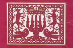 """Mizrach-Shiviti by Yehudit Shadur. Papercut, maroon on white background, depicting a pair of birds and a pair of stylized stags flanking a five-branched Menorah surmounted by a coronet and the word """"Mizrach."""" Signed in English and in Hebrew. 11.5"""" x 14.5"""" (28 x 36 cm) Estimate $1,500 – 2,500"""