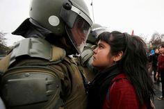 Uczestniczka demonstracji patrzy w oczy policjanta podczas zamieszek w Chile