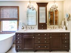 Dark wood vanity enriches this traditional bathroom and creates a beautiful focal point. The chandeliers above each sink create an elegant feel for this traditional bathroom.