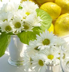 Daisies in silver mint julep cups and lemons in glass bowls make a nice spring table for a day time garden wedding