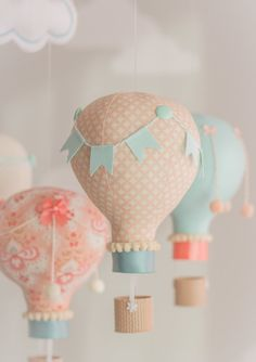 Aqua and Coral hot air balloon baby mobile. The photos show 5 hot air balloons floating under two puffy clouds. Each balloon is hand made from