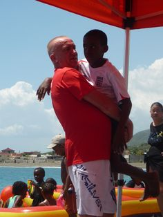 Digicel Staff Volunteer bonding with a child attending the Surfing for Autism event held on March 24, 2012 at Bull Bay, Jamaica