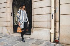 Buyer e co-founder do Gallerist, Mariana Cassou veste poncho listrado Mixed, tricot cinza, jeans preto destroyed, chapéu preto, botas pretas, bolsa bege e óculos escuros, street style, paris fashion week.