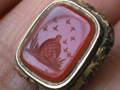 A Victorian intaglio seal of honey bees flying around the hive; a symbol of productive industry.