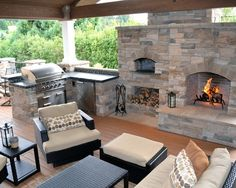 Hardwood flooring, black wicker furniture, and exposed ceiling beams fill out this outdoor kitchen space. A large fireplace stands within the stone enclosure holding countertops, grill, and brick oven.