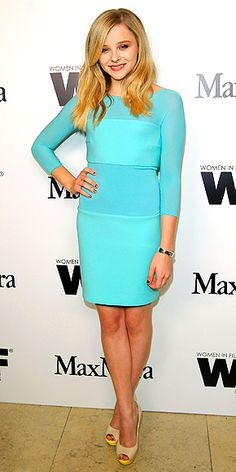 CHLOË MORETZ in a slim teal Max Mara dress, metallic cuff and nude sandals with a subtle pop of color at the platform.