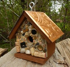 Travel Inn..... Embossed copper look roof. Base, back, sides and roof line stained in 10 yr. deck stain, in brown color. Embellished with river rock, polished rocks and metal trinkets. Will look great as indoor decor' or let your wrens, nuthatches, or chickadees enjoy the beauty of a new home in your garden or yard.  Removable base for easy clean out.