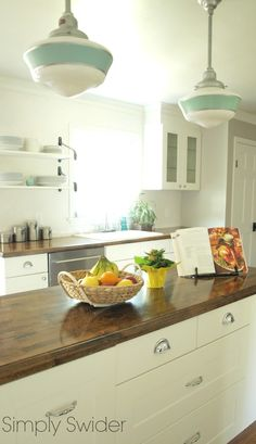 Barn Light Electric's Primary Schoolhouse Pendant in jadite and galvanized metal add vintage charm to a white kitchen.