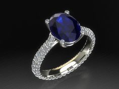 A rich micropavè of brilliant cut diamonds embraces a natural blue sapphire. Perfect as an engagement ring! From Luxedogems.com