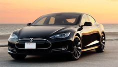 Tesla Model S with Sunset & orange hughes of beach in the background.