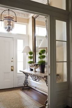 Entryway. two lamps. topiarys and a mirror