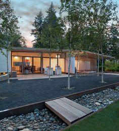 """""""They wanted the new cabin to make a 'L' shape with the older cabin, but I convinced them to mimic the old cabin on the opposite side,"""" architect D'Arcy Jones says. """"So the new site has two buildings across from each other, like an equal sign."""" Birch trees grow between the cabins in a shared courtyard."""
